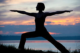 Silhouette of woman in warrior yoga pose at sunset